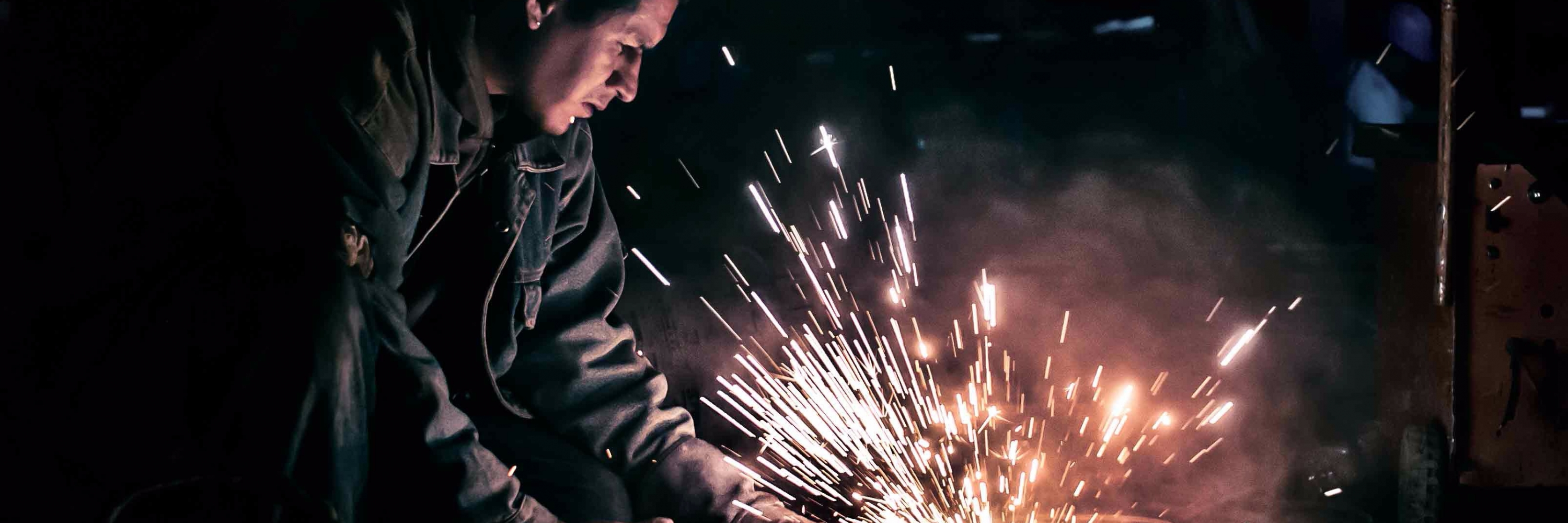 A man grinding metal in work overalls, sparks flying, showing why businesses might need Employers' Liability Insurance and Public Liability Insurance