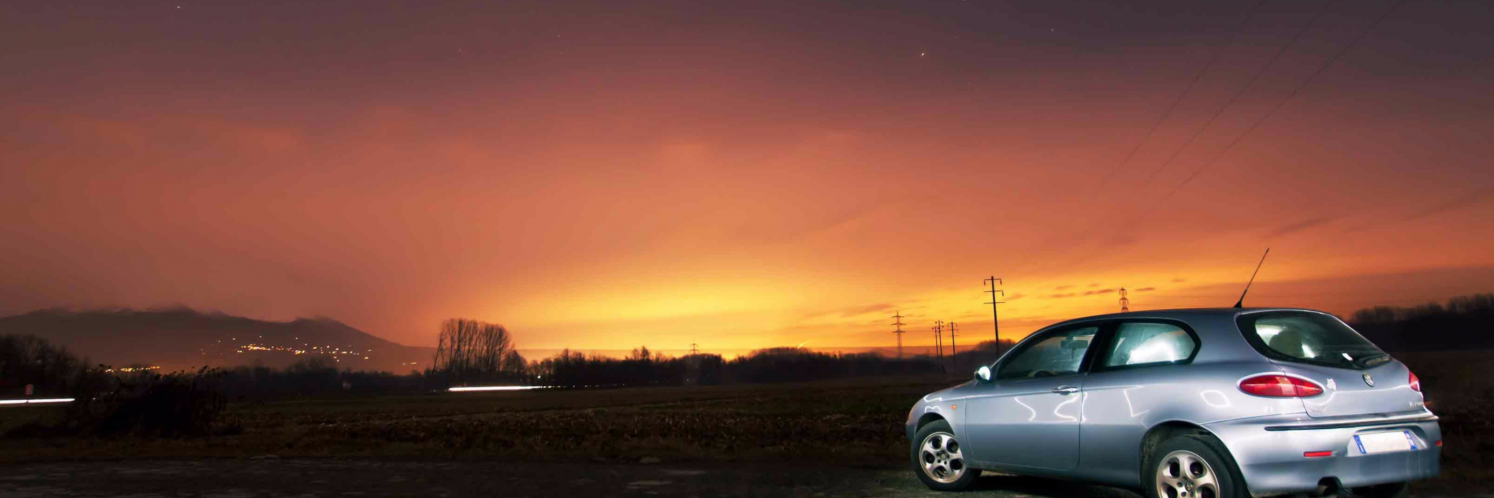 A car, at a remote location as the sun sets over the hills, for which P F Spare Insurance Brokers can arrange car insurance